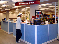 Reference Services - 1st floor Library; student receiving assistance at Reference Desk