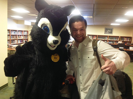 Student posing with University Libraries mascot, Rocky at 2014 Welcome Week event.